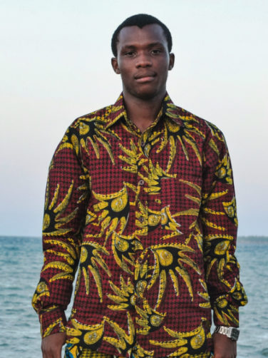 Men's Peacock African Print Long Sleeve Shirt worn by a model on the beach in Tanzania