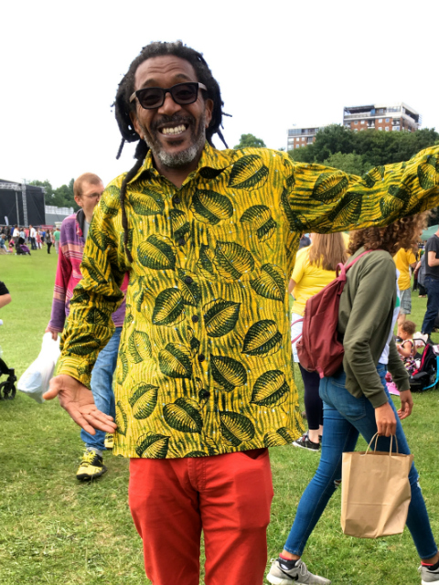 Men's yellow leaf African print long sleeve shirt customer wearing at Africa Oye Festival in Liverpool UK