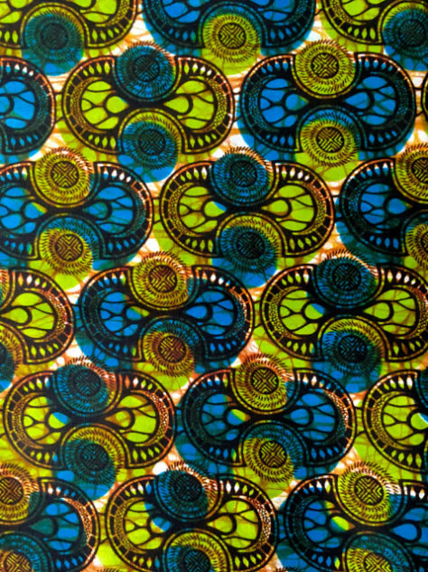 Green African print fabric used to make African style shirts close up