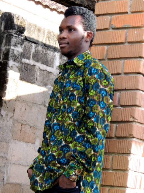 Men's Green African shirt with long sleeves and side pocket worn by a model in Tanzania side view