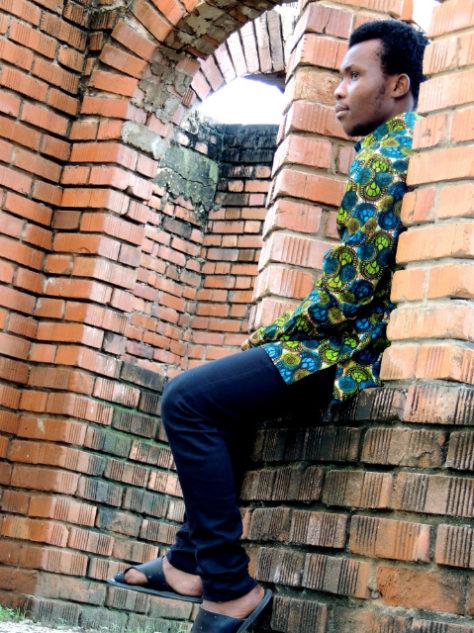 Men's dark green African shirt long sleeves model wearing in Tanzania sat down side view