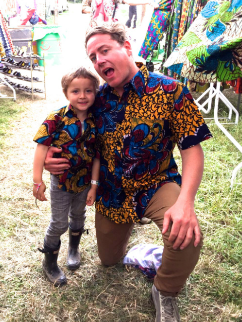 Father and son wearing matching Kitenge African print style shirts with short sleeves at Glastonbury Festival UK