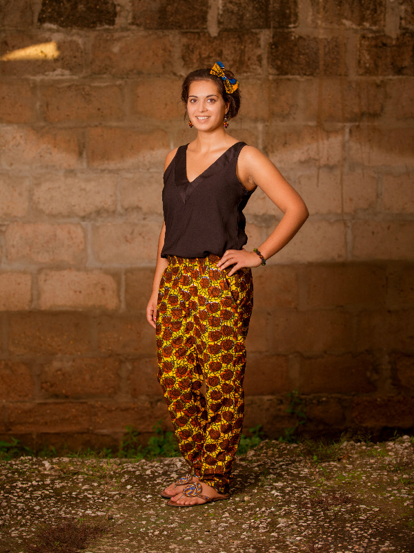 Model wearing Kitenge unisex brown african print trousers in Tanzania photoshoot