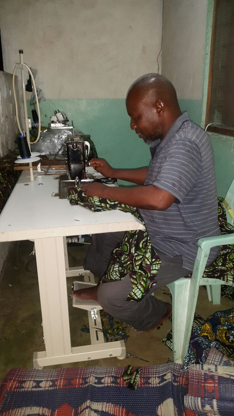 Abdallah kitenge's main tailor working from his home with sewing machine