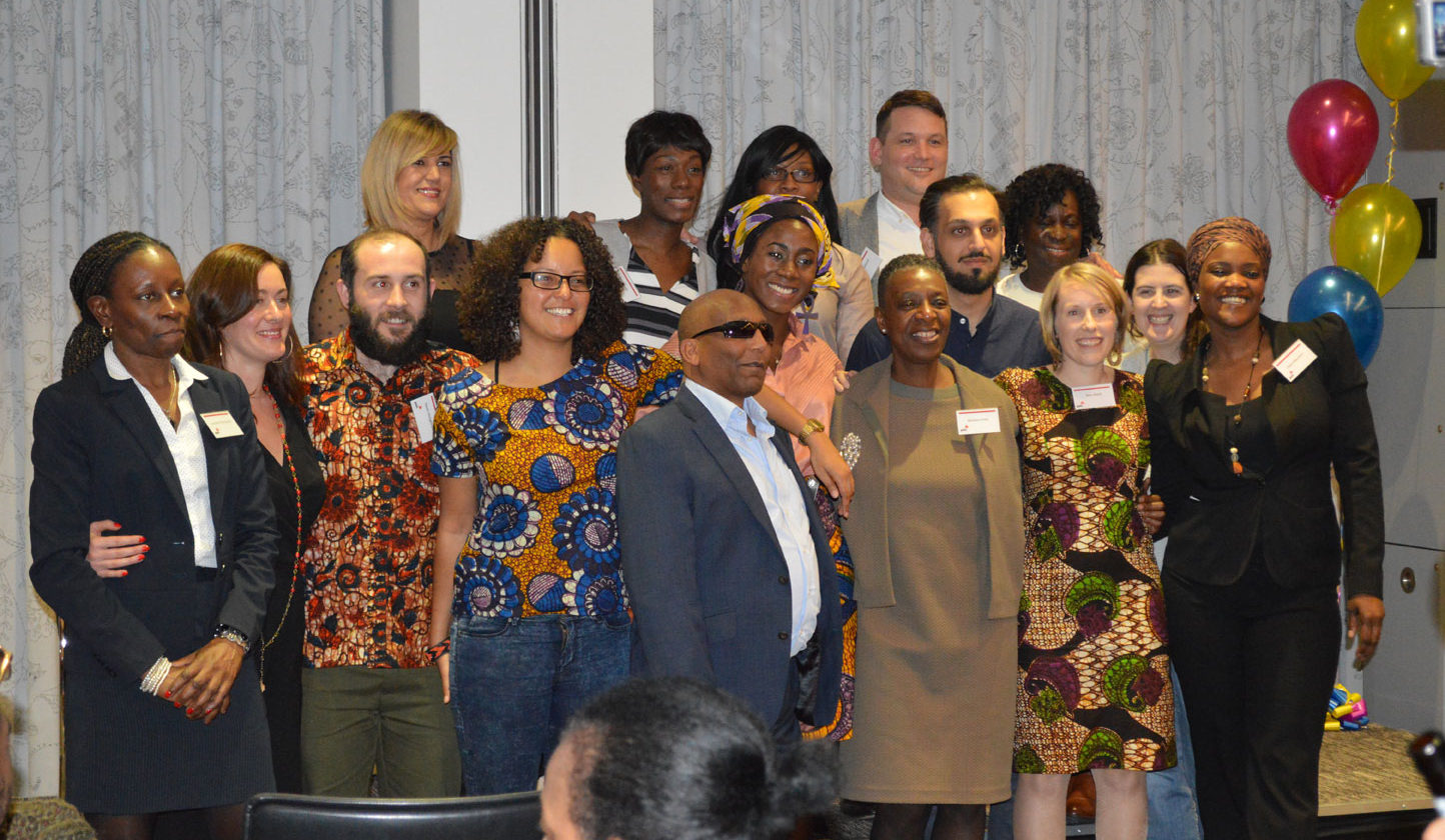 Kitenge Store founder Sian wearing an African print dress standing with her course mates at the School for Social Entrepreneurs Fellowship Graduation event at PwC offices in Central London