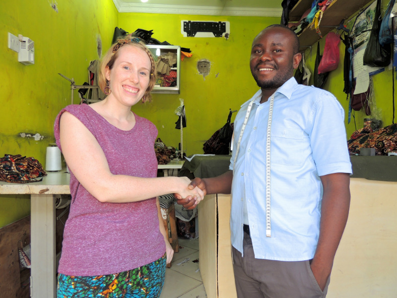 Sian and Hassan shaking hands outside Kitenge's main tailor's new workshop in Tanzania