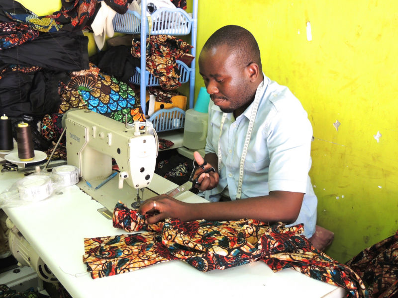 Kitenge's newest tailor called Hassan making a men's shirt in the workshop in Tanzania