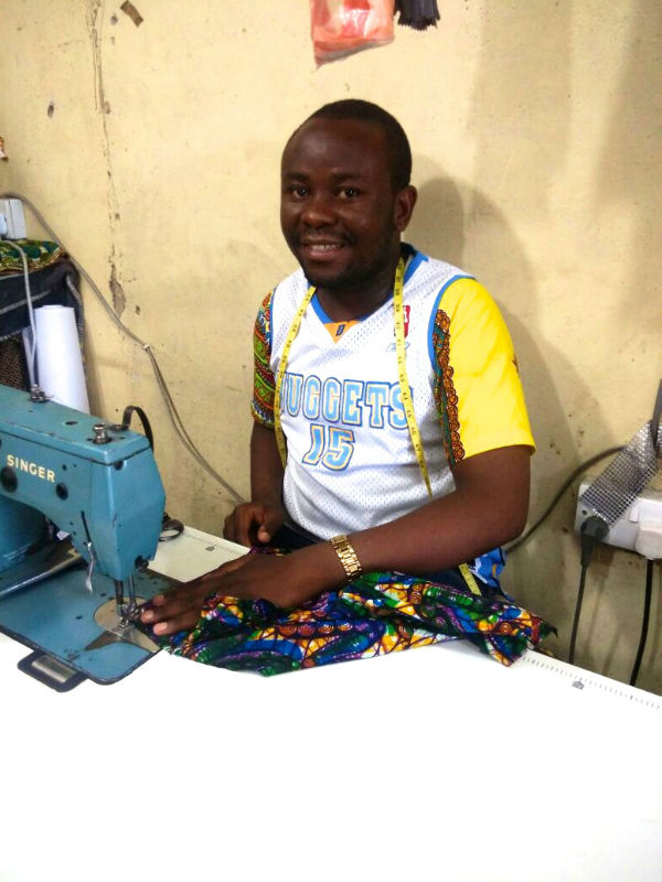 Kitenge tailor called Hassan with Singer sewing machine in shared workshop in Tanzania