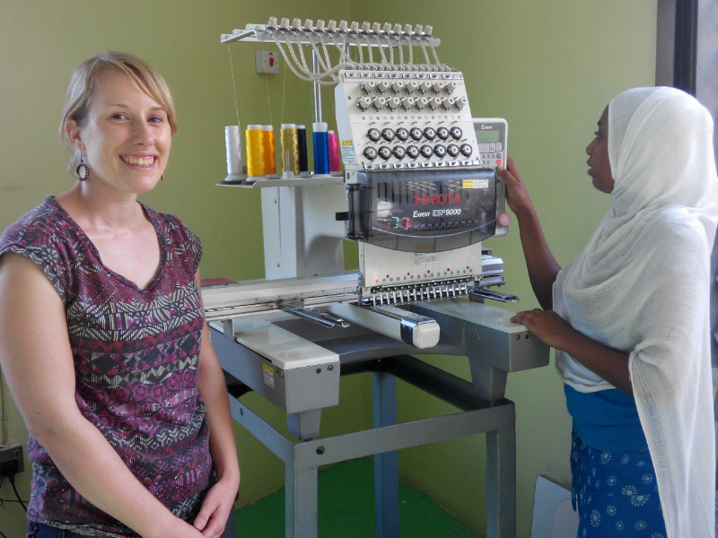 Sian and Asia standing next to the computerised embroidery machine which makes all of Kitenge Store's brand and size labels