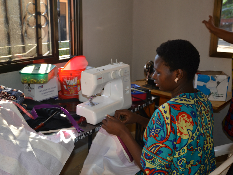 Abigail sewing in Kitenge tailor Betty's old workshop in Tanzania before expanding her business premises