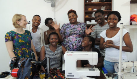 Betty with her talented team of tailors and Kitenge Store Founder Sian standing inside her newly built workshop in Tanzania laughing together