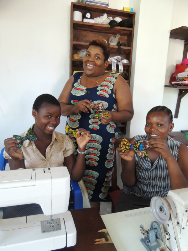 Betty with her tailors Lucy and Levina presenting their finished kitenge African print hair clips handmade using recycled offcut fabrics in Tanzania