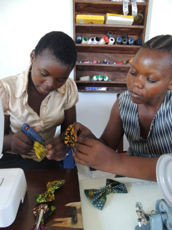 Kitenge tailors Lucy and Levina making African print hair clips using recycled offcut fabrics by hand in Tanzania