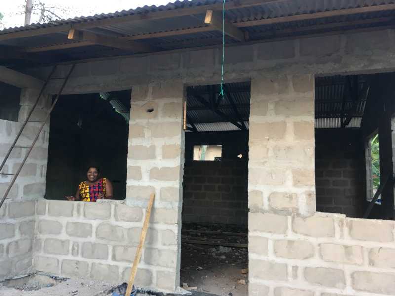 Kitenge tailor called Betty standing inside her newly built worksop in Tanzania before the windows and front door is put in
