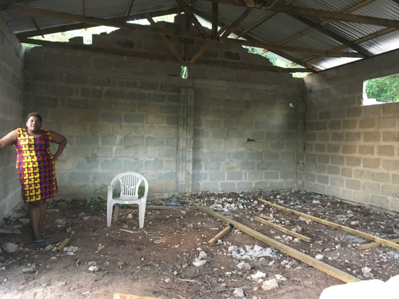 Kitenge tailor called Betty standing inside her newly built larger workshop in Tanzania