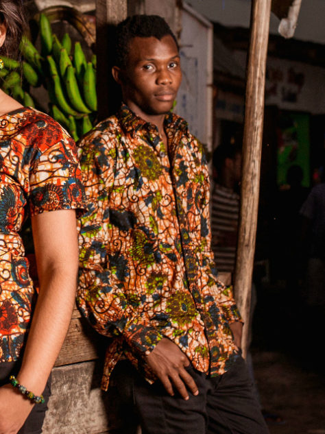 Men's green floral African print long sleeve shirt model wear Tanzania fruit and vegetable stall