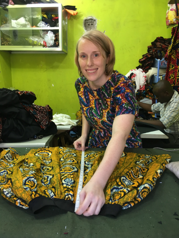 Kitenge founder Sian quality checking a newly handmade yellow African print skirt during production at our main tailors cutting table at his own workshop in Tanzania