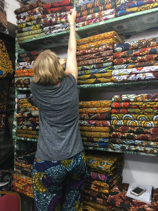 Kitenge founder Sian standing on a chair at the market in Tanzania trying to reach the best African wax print fabrics to make our modern afrocentric clothing