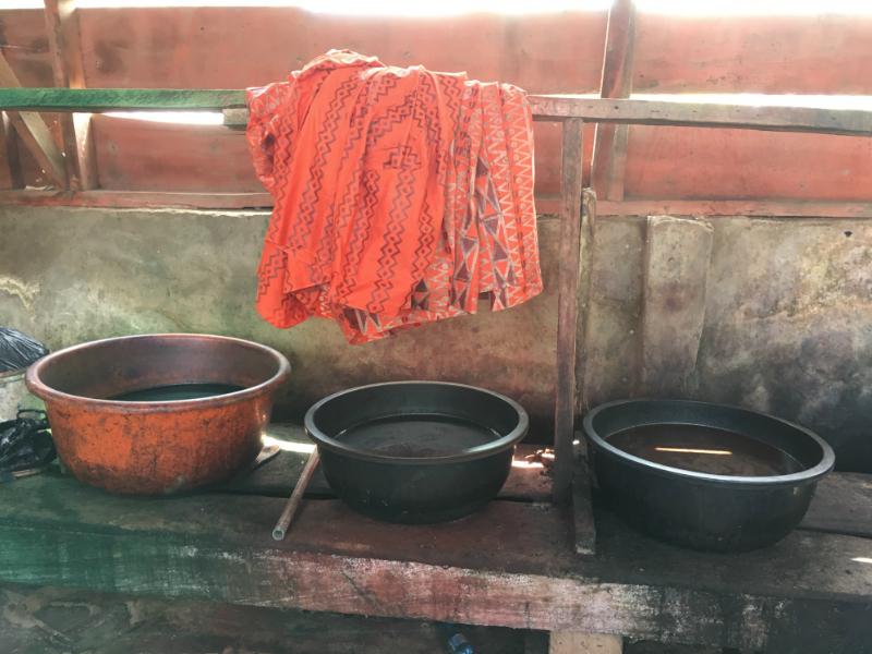 Dye baths inside a traditional batik fabric making workshop in Ghana