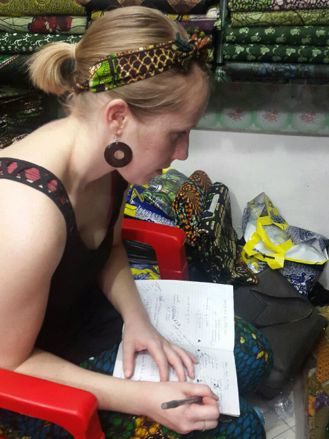 Kitenge founder Sian carefully calculating African print fabric consumption to make modern afrocentric clothing at the market in Tanzania East Africa
