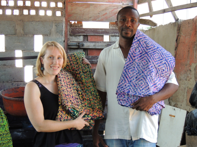 Kitenge Store Founder Sian visited Daniel at his batik making workshop in Ghana West Africa holding two different finished colourful fabric designs used to make modern afrocentric clothing