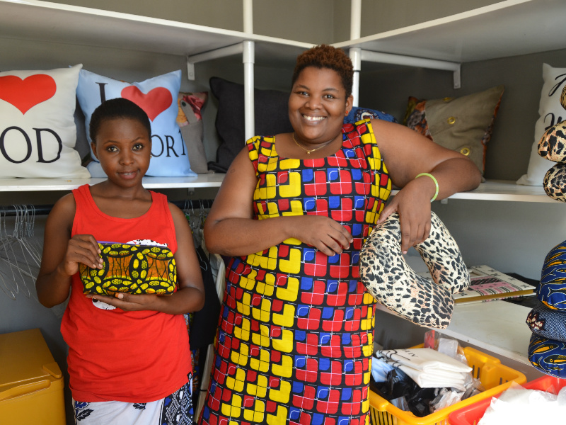 Kitenge-accessories-tailor-Betty-with-her-manager-upendo-standing-inside-her-shop-in-Tanzania-with-some-of-their-handmade-African-print-cushions