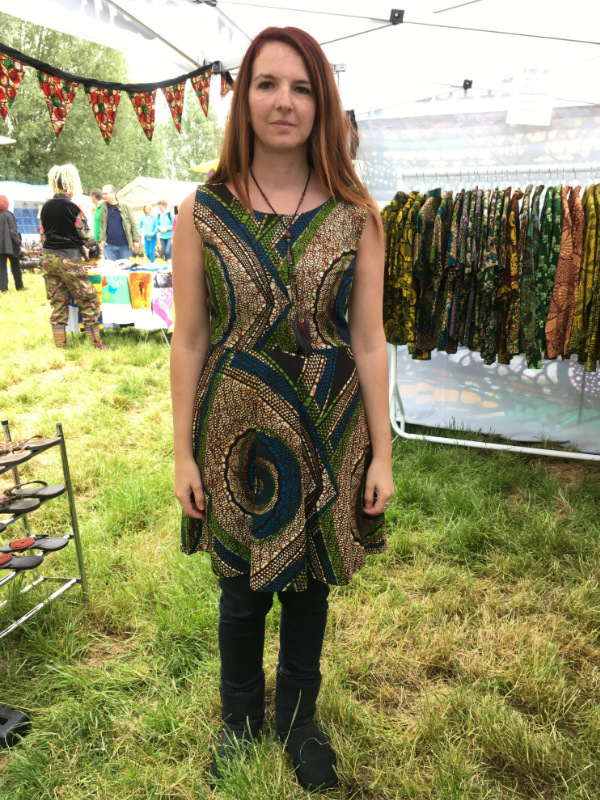 A Kitenge customer wearing her new sleeveless African print dress at Strawberry Fair 2016 in Cambridge, UK
