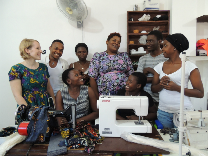 Kitenge founder Sian standing with our accessories tailor better and her team of talented tailors inside their brand new larger workshop in Tanzania in front of a table of sewing machines