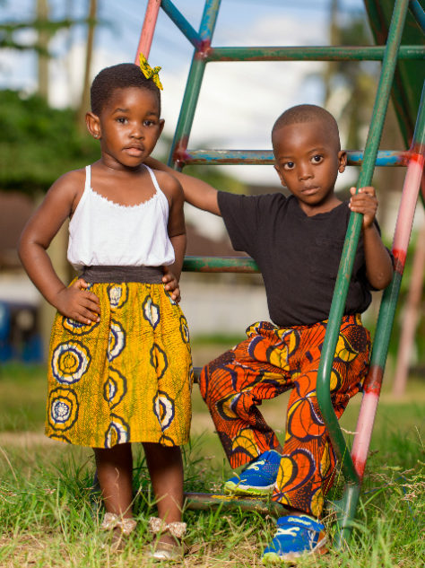 African clothing for kids models wearing at a playground in Tanzania elasticated skirt and trousers pants