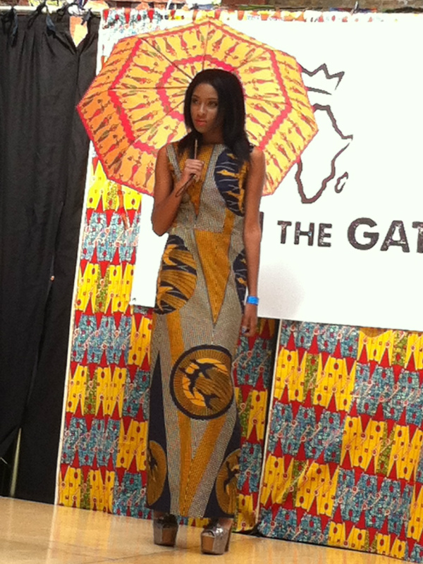 Model wearing an African print maxi dress on the catwalk at Old Spitalfields Market in London, UK