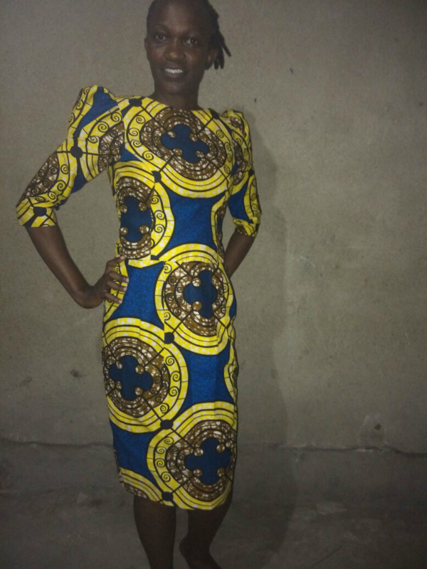 A bespoke tailor made African print pencil dress with shoulder pads worn by a women in Tanzania
