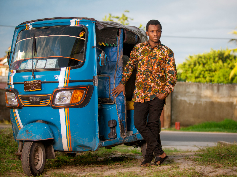 Tanzanian male model wearing a green floral African print shirt with long sleeves by Kitenge Store standing outside next to a tuk tuk