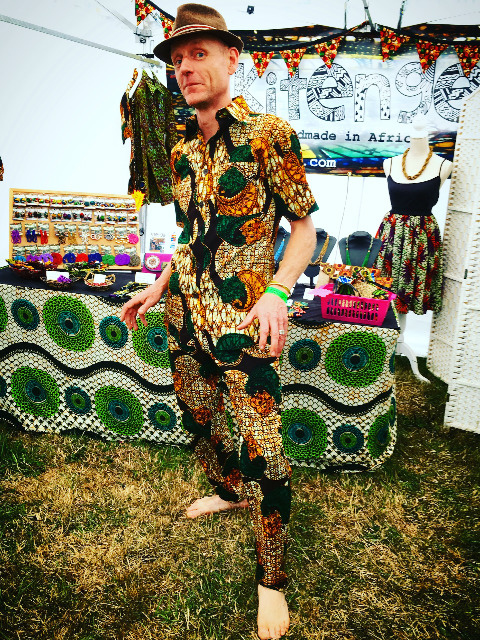 kitenge customer wearing a matching African print shirt and African print trousers at Beautiful Days Festival in Devon UK