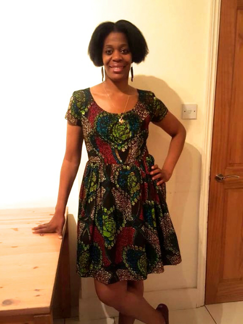 Kitenge customer wearing her African print dress fit and flare style with bold statement earrings