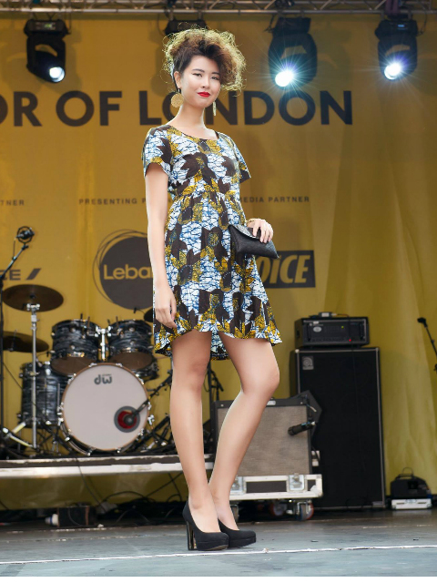 Model wearing a Kitenge African print dress holding a small black clutch bag during a fashion show at Africa on The Square in Trafalgar Square London