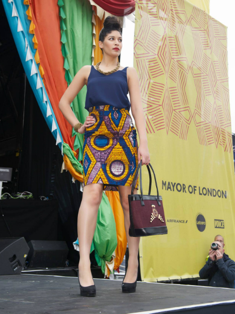 A model wearing a Kitenge African print skirt with a matching African beaded handbag handmade in Tanzania on the catwalk at Africa on The Square in Trafalgar Square London