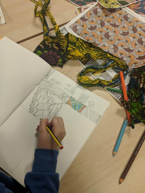 Child sketching African print clothing fabrics in school art class