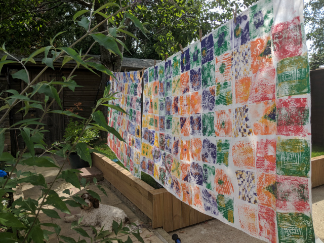 Finished children's African print inspired artwork hanging outside to dry on washing line in garden