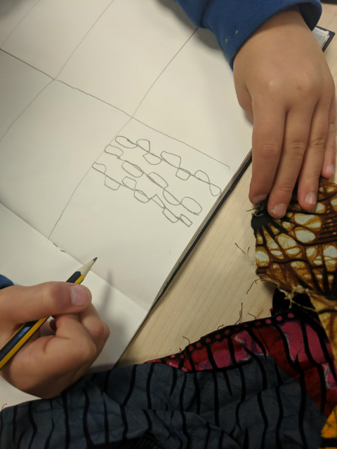 Year 2 pupil drawing with pencil a traditional African clothing fabric pattern in their sketchbook during an art class